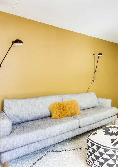 47. Sala com parede amarela decorada com sofá cinza moderno e arandela articulável preta – Foto: Dcore Você