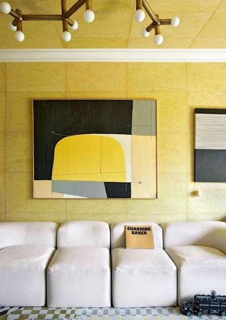 49. Sofá branco moderno para decoração de sala com parede amarela com quadros grandes – Foto: Pinterest