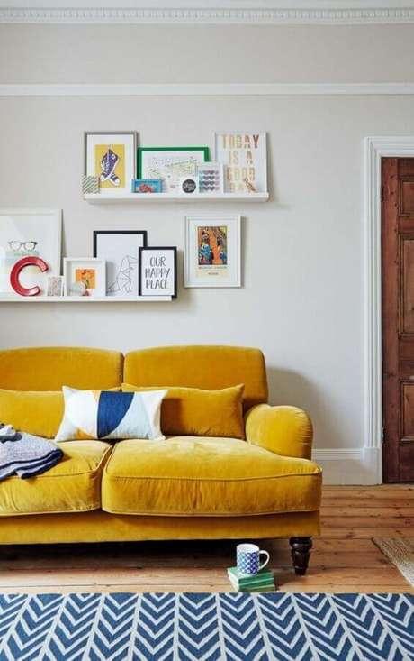 52, Sofá para sala amarela e branca decorada com prateleiras para quadros – Foto: Histórias de Casa