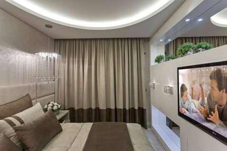 70. Quarto de casal com painel para tv branco e moderno – Projeto: Iara Kilaris