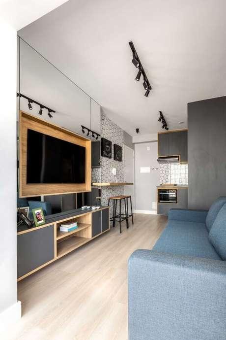 1. Sala de estar com painel para tv espelhado e de madeira – Projeto: Zark Studio Lab