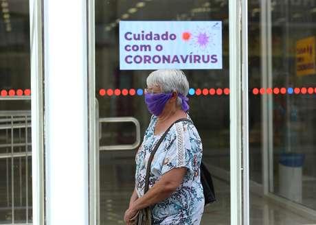 Idosa usa lenço como máscara de proteção contra o novo coronavírus enquanto passa por em agência bancária em Curitiba