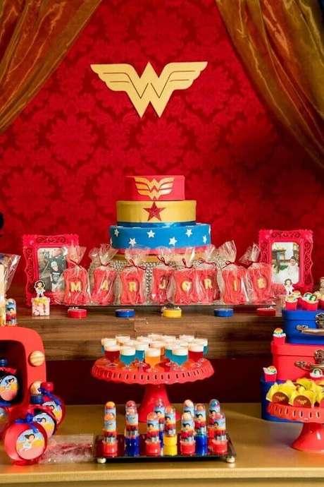 1. Ideia de decoração para mesa de festa da Mulher Maravilha com painel vermelho – Foto: Papo Glamour