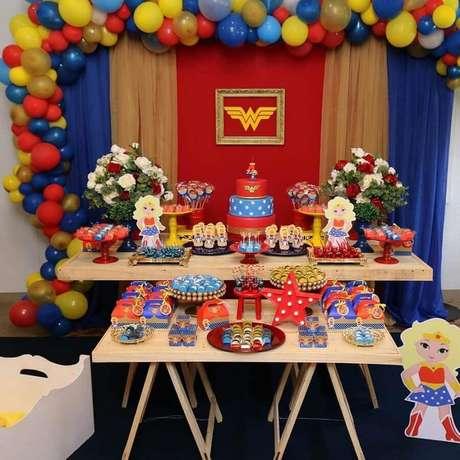 24. Decoração de festa Mulher Maravilha simples com mesa de cavalete e painel com balões coloridos – Foto: Patrícia Freitas