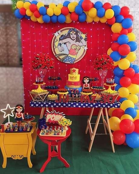 26. Festa Mulher Maravilha simples decorada com arco de balões e pisca pisca no painel – Foto: Tio Festeiro