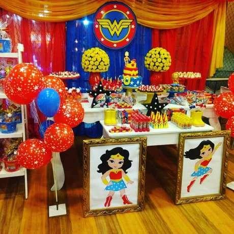 29. Linda decoração de festa Mulher Maravilha com quadros grandes, arranjo de flores amarela e balões ao lado da mesa principal – Foto: Meninas Festeiras