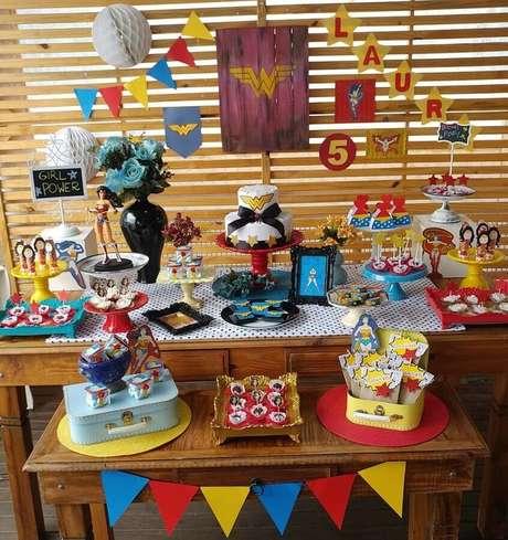 38. Decoração para festa Mulher Maravilha simples com painel de pallet e mesas de madeira – Foto: Festejar