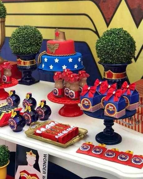 40. Docinhos em forminhas personalizadas para mesa decorada de festa Mulher Maravilha – Foto: Olaria da Festa