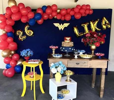 42. Decoração de festa Mulher Maravilha simples com painel azul e balões vermelhos – Foto: Liliane Rodrigues