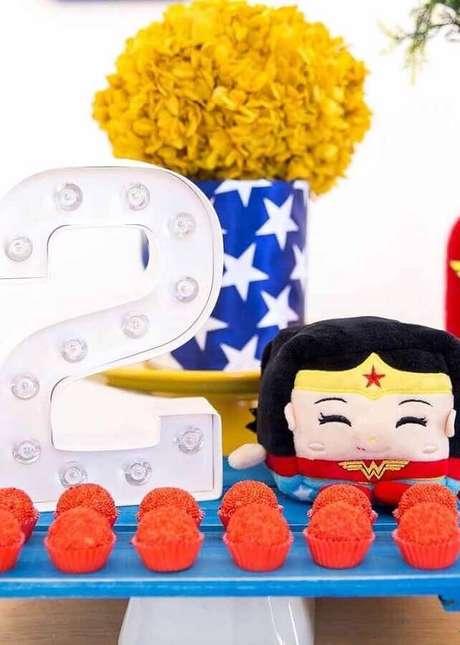 51. Luminária de led para decoração de festa de aniversário da Mulher Maravilha com arranjo de flores amarelas – Foto: Home Fashion Trend
