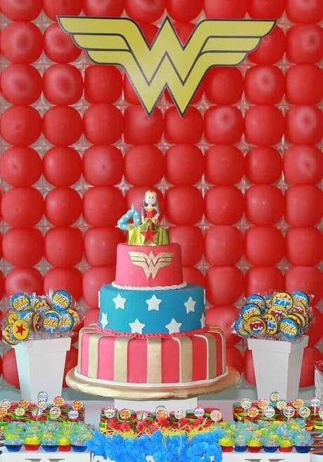 55. Painel de balões vermelhos e bolo 3 andares decorado para festa de aniversário da Mulher Maravilha – Foto: Kara's Party Ideas