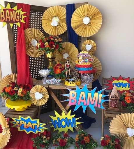 58. Móveis rústicos para decoração de festa de aniversário Mulher Maravilha com arranjos de flores – Foto: Patty Decor