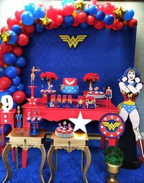 59. Painel azul decorado com balões para festa Mulher Maravilha com mesa vermelha e dourada – Foto: Pinterest