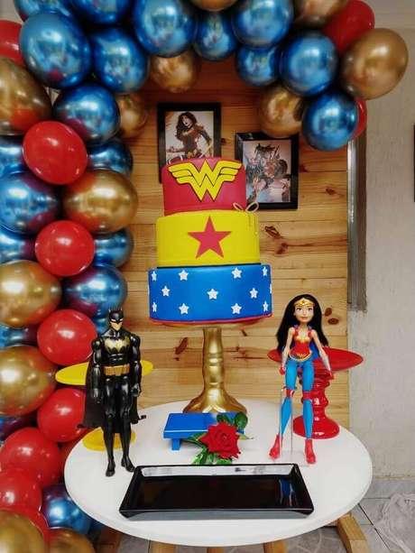 60. Painel de balões com acabamento metalizado para decoração de festa Mulher Maravilha com boneco do Batman e Mulher Maravilha – Foto: Elo7
