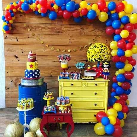 61. Painel de madeira decorado com arco de balões e móveis coloridos para festa de aniversário Mulher Maravilha – Foto: A Minha Festinha