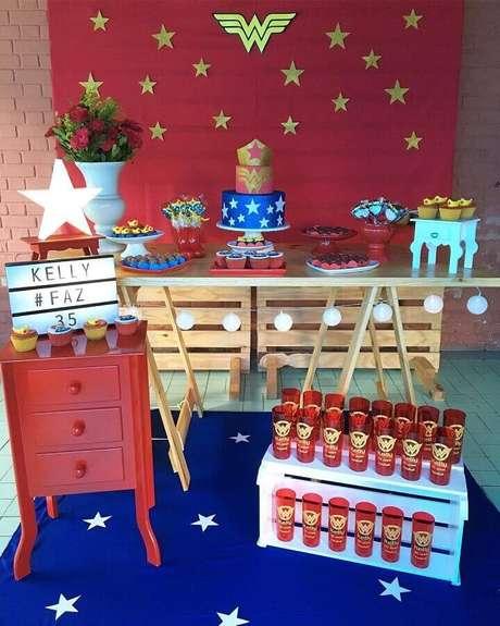 65. Painel vermelho decorado com estrelas douradas para festa Mulher Maravilha simples – Foto: Mirabella Festas