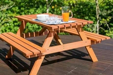 14. A mesa de madeira com banco também fica bem na área externa – Foto: Madeira madeira