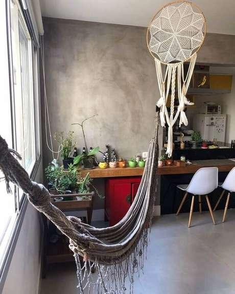 60. Decoração para sala com parede de cimento queimado e filtro dos sonhos em cores neutras – Foto: Artezz
