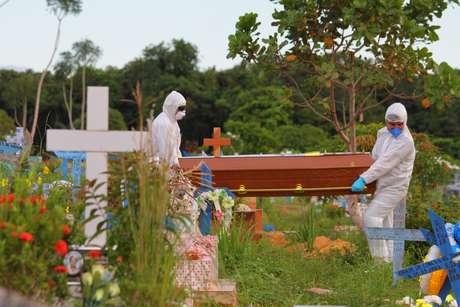 Operários com roupas de proteção realizam enterro em Manaus, no Amazonas