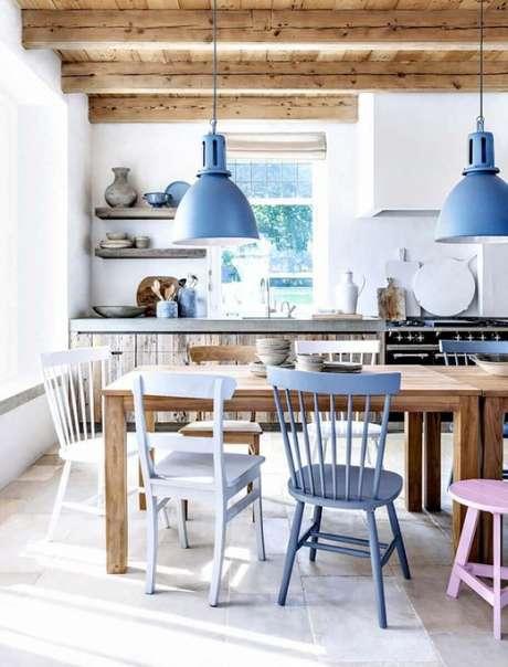 21. Decoração rústica com pendentes para cozinha com mesa de madeira e várias cadeiras diferentes