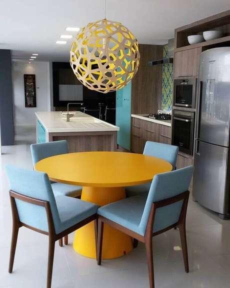 66. Modelo diferente de pendente redondo para cozinha decorada com mesa amarela e cadeiras azuis – Foto: Karen Pedrosa