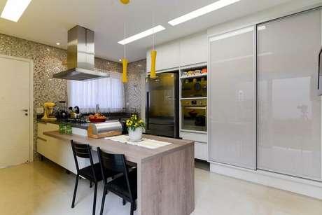 15. Modelo delicado de pendente amarelo para cozinha com bancada de madeira.
