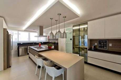 43. Decoração com pendentes para cozinha sobre a bancada com ilha planejada com cooktop