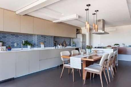 78. Pendentes para cozinha ampla decorada com mesa de madeira integrada a ilha – Foto: Tria Arquitetura