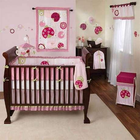 29. Decoração simples de quarto de bebê rosa com berço de madeira escura – Foto: Pinterest