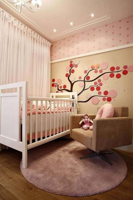 43. Poltrona bege para decoração de quarto de bebê rosa com papel de parede de bolinhas – Foto: Pinterest