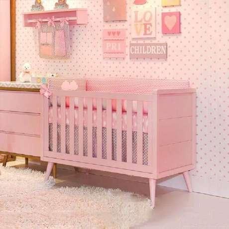 47. Quarto de bebê rosa decorado com papel de parede de bolinhas e vários quadrinhos – Foto: Pinterest