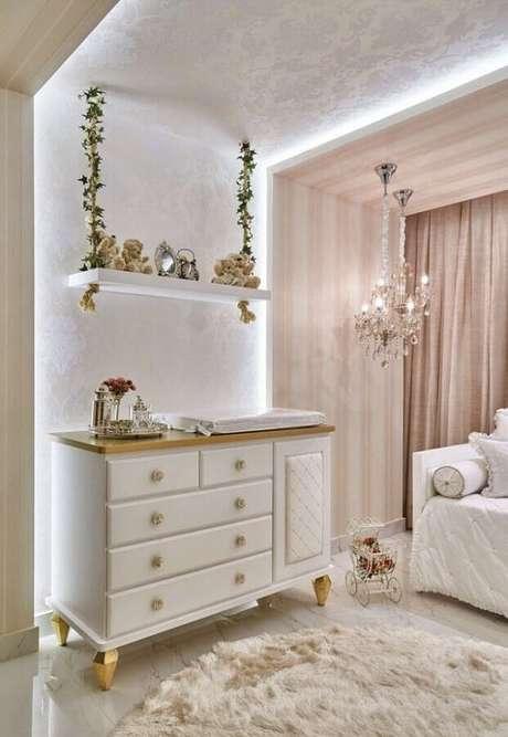 53. Quarto de bebê rosa e branco decorado com linda prateleira suspensa e lustre de cristal – Foto: Futurist Architecture