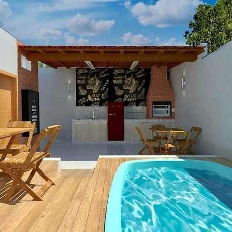 14. Área gourmet simples com churrasqueira e piscina – Foto: Pinterest