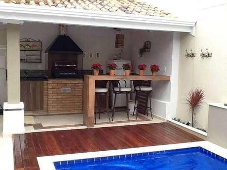 12. Área gourmet externa simples com piscina e bancada de madeira para refeições – Foto: Pinterest