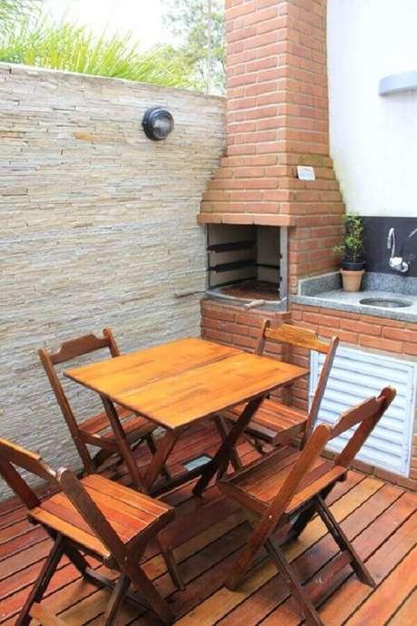 17. Área gourmet pequena e simples com churrasqueira de alvenaria e jogo de mesa com cadeiras de madeira – Foto: Espaço Casa