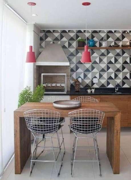 18. Área gourmet pequena e simples decorada com pendentes vermelhos sobre bancada de madeira e azulejo com desenho geométrico – Foto: