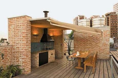 22. Área gourmet rústica e simples decorada com churrasqueira de vidro e mesa de madeira – Foto: Francisco Barros