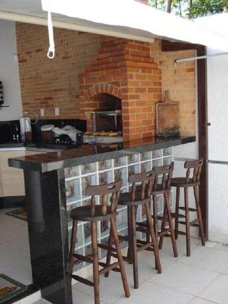 27. Banquetas de madeira para decoração de área gourmet simples com churrasqueira – Foto: Revista VD