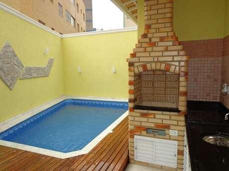 29. Área gourmet simples com churrasqueira e piscina – Foto: Achou Mudou