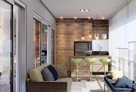 30. Varanda de apartamento decorada com área gourmet simples com churrasqueira e banquetas verdes – Foto: Pinterest