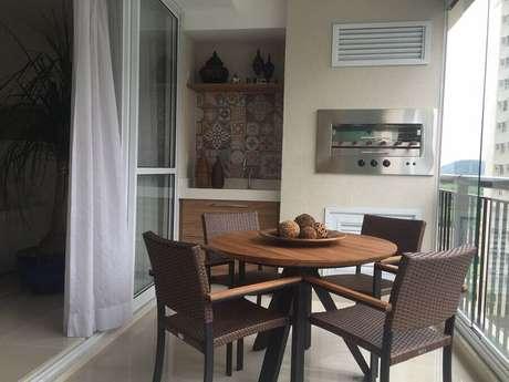 33. Varanda de apartamento com área gourmet simples e pequena com churrasqueira e mesa redonda de madeira – Foto: Isabella Machado