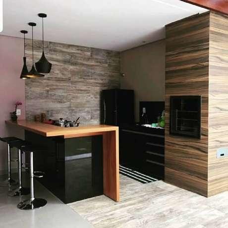 35. Decoração de área gourmet simples com churrasqueira e bancada de madeira – Foto: Pinterest