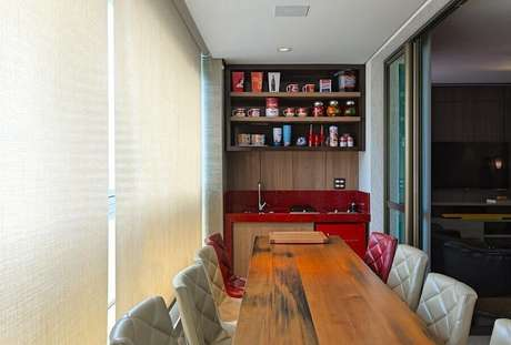 36. Decoração de área gourmet pequena e simples com mesa de madeira e bancada vermelha – Foto: Mariana Borges e Thaysa Godoy
