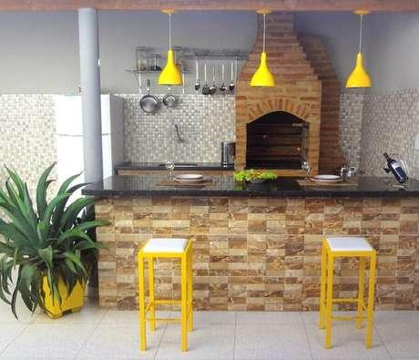 2. As banquetas e pendentes amarelos fizeram toda a diferença na decoração dessa área gourmet simples e pequena – Foto: CasaCoração