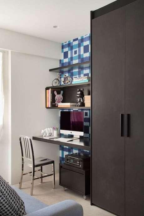 16. Cantinho de estudo simples decorado com móveis pretos e papel de parede azul – Foto: Decoist