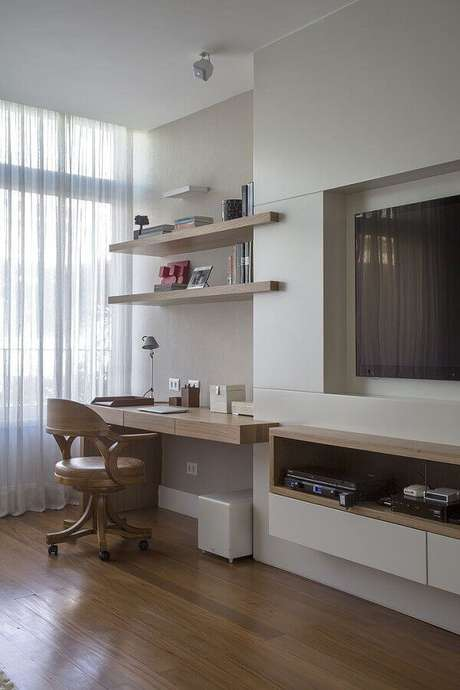18. Cantinho de estudo na sala decorada com bancada de madeira planejada – Foto: Decoholic