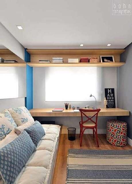 7. Decoração para cantinho de estudo no quarto com bancada de madeira e cadeira vermelha – Foto: Simples Decoração