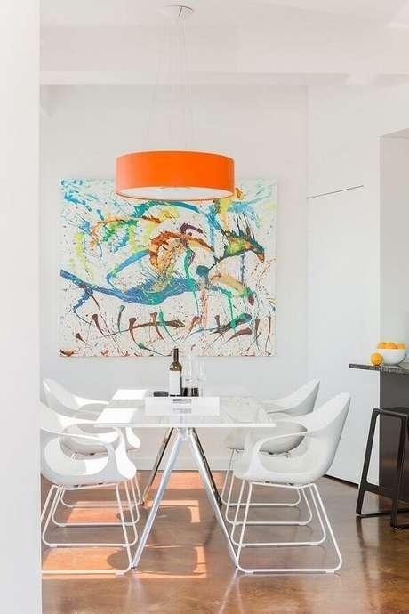 16. Decoração minimalista para sala de jantar toda branca com pendente laranja e quadros abstratos coloridos – Foto: Paquette Associates