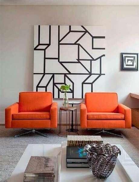18. Poltronas laranjas e quadro abstratos geométricos para decoração de sala – Foto: Casa Prosa Decor