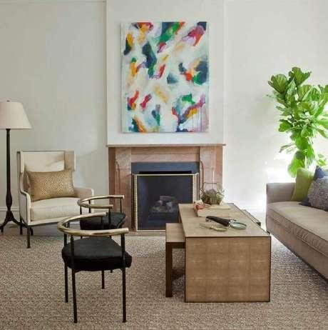 21. Quadros abstratos coloridos para decoração de sala clássica com lareira e poltrona bege – Foto: Webcomunica